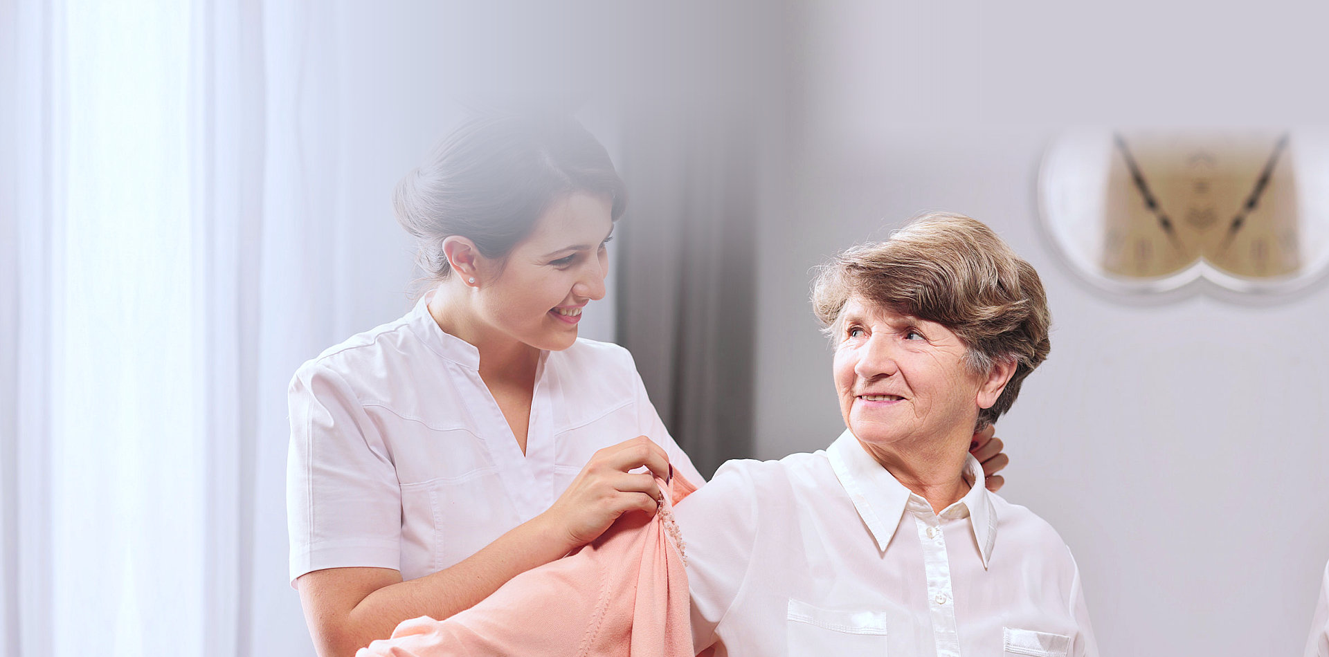 caregiver helping senior woman to wear clothes