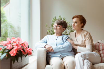 elder woman and caregiver looking at the window