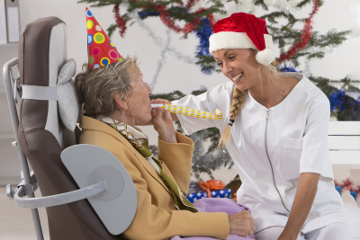 elder woman and the caregiver with a santa hat
